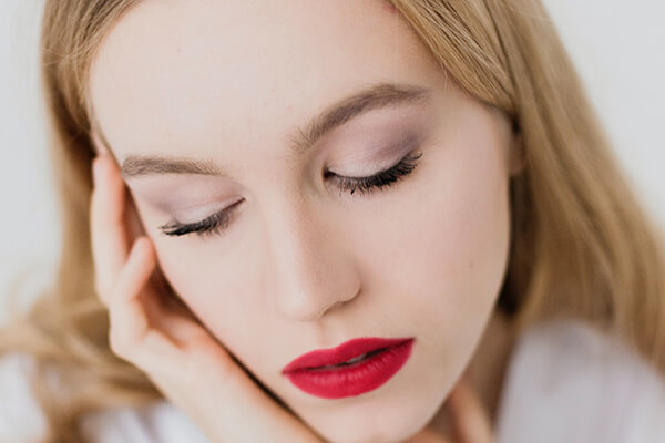woman touching face with red lips