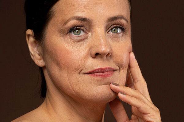 older woman touching face