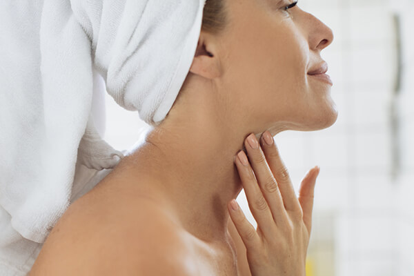 woman on towel touching neck
