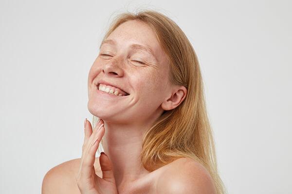 smiling woman touching neck
