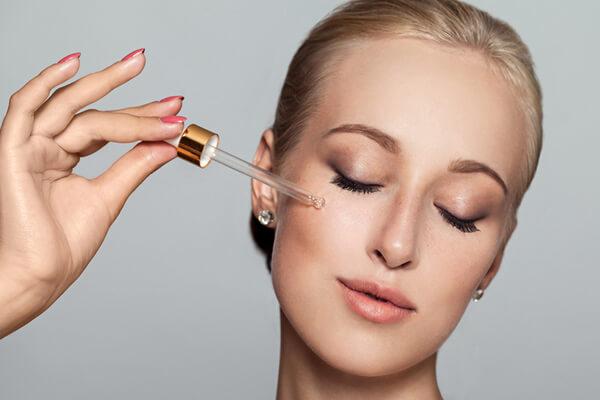 woman applying facial oil on face